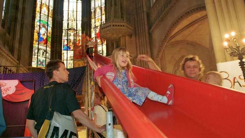 Ein Mädchen rutscht auf einer Rutschbahn in einer Kirche.