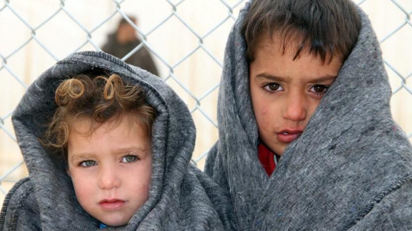 Zwei Kinder in Syrien in Decken gehüllt, die sie von einem Nothilfeprogramm erhalten haben.