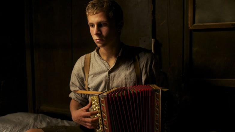 Das Bild zeigt eine Szene aus dem Film «Der Verdingbub». Ein Junge spielt in einem Zimmer Ziehharmonika und blickt dabei traurig in den Raum.