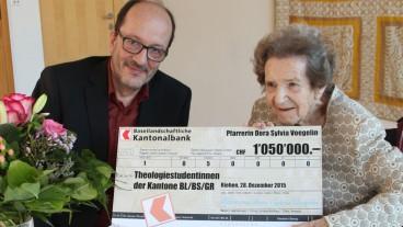 Pfarrerin Dora Sylvia Voegelin übergibt den Check für den Dora Sylvia Voegelin-Fonds an Pfarrer Martin Stingelin, Kirchenratspräsident der reformierten Kirche Baselland.