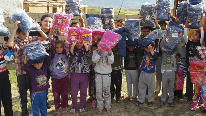 Hilfe für alle, unbesehen ihrer Religion: Kinder freuen sich an einer Lieferung Textilien.