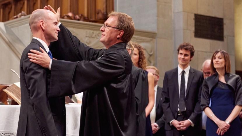 Ordinationsfeier im Zürcher Grossmünster: Kirchenratspräsident Michel Müller setzt einen neuen Pfarrer in sein Amt ein (August 2015).