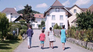 Vier Kinder spazieren durch ein Schweizer Dorf.