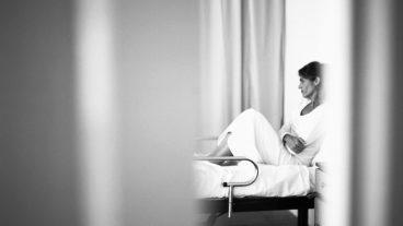 Blick durch einen Vorhang auf ein Krankenbett mit einer Frau, die ihre Arme verschränkt.