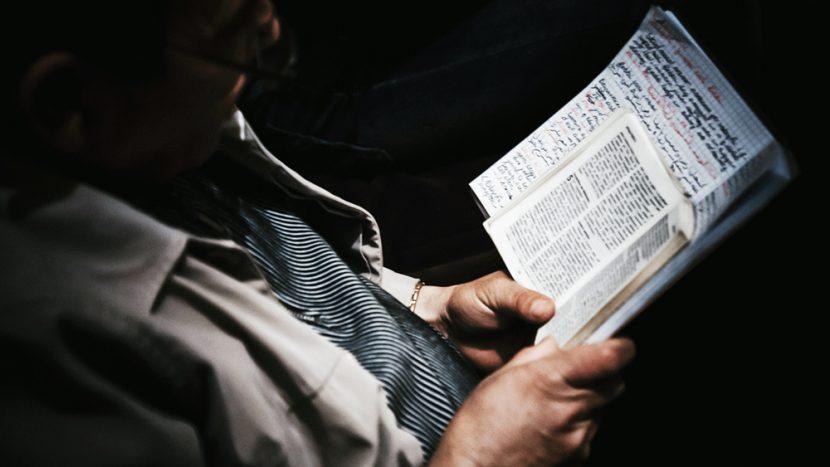Mann hält Buch und Notizen in den Händen.